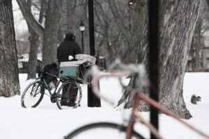 A man with a bicycle stands in the snow.